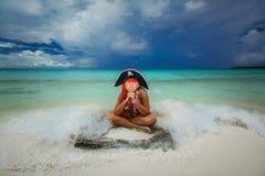 做滑稽的恼怒的面孔的美丽的矮小的海盗女孩,坐热带海滩反对平静的海洋和黑暗的剧烈的天空 免版税库存图片