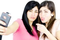 做滑稽的面孔的女孩采取selfie 免版税库存照片