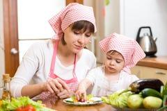 做滑稽的面孔的妈妈和孩子女孩由菜在板材 免版税图库摄影