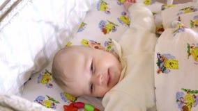做滑稽的面孔的新出生的女婴男孩微笑和舒展,当醒在自己小的床上在明亮的早晨时 股票录像
