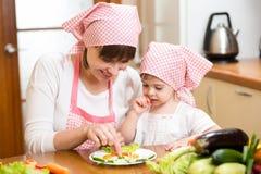 做滑稽的面孔的母亲和孩子由菜在板材 免版税图库摄影