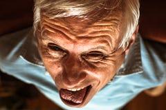 做滑稽的面孔的老人 免版税图库摄影