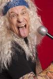 做滑稽的面孔的资深音乐家特写镜头,当唱歌在红色背景时 免版税图库摄影