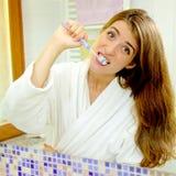 做滑稽的面孔的逗人喜爱的妇女,当洗牙在镜子前面时的卫生间里 图库摄影