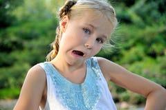 做滑稽的面孔的逗人喜爱的小女孩 免版税图库摄影