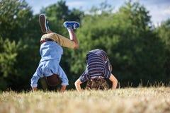 做翻筋斗的两个男孩 图库摄影