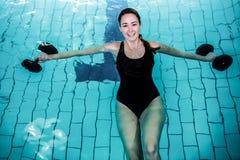 做水色有氧运动的适合的微笑的妇女 免版税库存照片