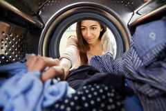 做洗衣店的妇女到达里面洗衣机 库存图片