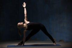 做延长的三角姿势的美丽的瑜伽妇女 免版税图库摄影