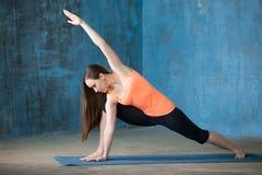 做延长的侧角姿势的运动的美丽的少妇 图库摄影