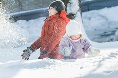 做暴风雪的兄弟姐妹孩子通过扔雪在冷淡的冬天晴天期间户外 库存照片