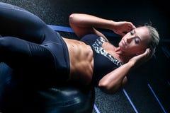 做ab的健身妇女在健身房球咬嚼 免版税库存图片
