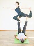 做acro瑜伽或对的男人和妇女室内瑜伽 库存照片