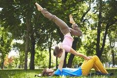 做acro瑜伽的逗人喜爱的夫妇在公园在一个晴天 免版税库存图片