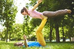做acro瑜伽的逗人喜爱的夫妇在公园在一个晴天 图库摄影