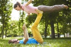 做acro瑜伽的逗人喜爱的夫妇在公园在一个晴天 库存图片