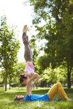 做acro瑜伽的逗人喜爱的夫妇在公园在一个晴天 库存照片