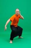 做asana的中年信奉瑜伽者的图象 图库摄影