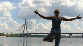做asana,瑜伽姿势的亭亭玉立的妇女,享受孑然和自由在大城市 影视素材