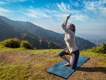 做Ashtanga Vinyasa瑜伽先进的asana的妇女 库存照片
