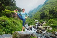 做Ashtanga Vinyasa瑜伽asana的妇女户外在瀑布 库存图片