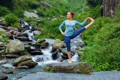 做Ashtanga Vinyasa瑜伽asana的妇女户外在瀑布 免版税图库摄影
