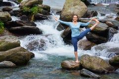 做Ashtanga Vinyasa瑜伽asana的妇女户外在瀑布 免版税库存照片