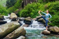 做Ashtanga Vinyasa瑜伽asana的妇女户外在瀑布 免版税库存图片