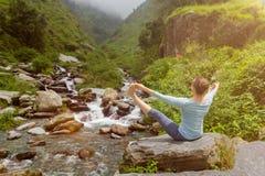 做Ashtanga Vinyasa瑜伽asana的妇女户外 免版税库存照片