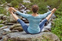 做Ashtanga Vinyasa瑜伽asana的妇女户外 库存图片