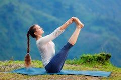 做Ashtanga Vinyasa瑜伽asana的妇女户外 免版税库存图片