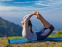 做Ashtanga Vinyasa瑜伽asana Dhanurasana的妇女-鞠躬姿势 库存照片