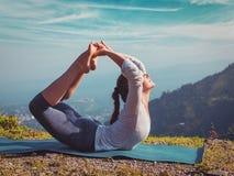 做Ashtanga Vinyasa瑜伽asana Dhanurasana的妇女-鞠躬姿势 免版税库存照片