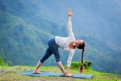 做Ashtanga Vinyasa瑜伽asana Parivrtta trikonasana的妇女 库存照片