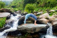 做Ashtanga Vinyasa瑜伽asana Urdhva Dhanurasana的妇女-  免版税库存图片