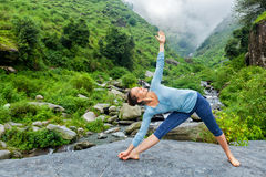 做Ashtanga Vinyasa瑜伽asana Utthita trikonasana的妇女 免版税图库摄影
