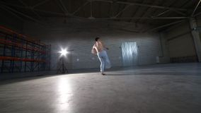 做capoeira元素和跃迁的一个运动人在有水泥地板和砖墙的屋子里 股票视频