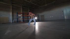 做capoeira元素的一个人-翻筋斗在他的头,不用手-在有水泥地板和砖墙的屋子里 股票视频