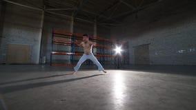 做capoeira元素-跃迁、轮和翻筋斗的一个运动人-在有水泥地板和砖墙的屋子里 股票录像