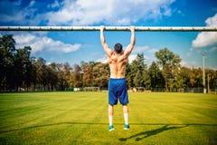 做chinups和核心训练的运动被修造的人在公园 健身在草地网球场的足球运动员训练,中坚分子的训练 免版税库存图片