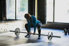 做deadlift的健身房的肌肉妇女 库存照片