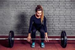 做deadlift的女运动员在健身房 免版税库存照片