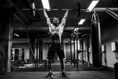 做deadlift的肌肉健身人在他的头的杠铃在现代健身中心 功能训练 免版税图库摄影