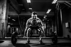 做deadlift的肌肉健身人在他的头的杠铃在现代健身中心 功能训练 库存照片