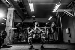 做deadlift的肌肉健身人在他的头的杠铃在现代健身中心 功能训练 免版税库存图片