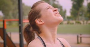 做exersices的年轻逗人喜爱的运动的健身女孩特写镜头画象在运动场在都市城市户外 股票视频