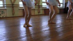 做exrcises的女孩的腿在芭蕾教训期间在磨损的教室 股票录像