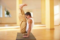 做handstanding的瑜伽的一个年轻大力士在瑜伽演播室行使- Urdhva Brahmachariasana 免版税图库摄影