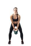 做kettlebell与12公斤的坚强的健身女孩正面图摇摆锻炼 免版税库存图片
