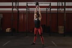 做kettlebell摇摆锻炼的年轻白种人体育妇女 库存照片